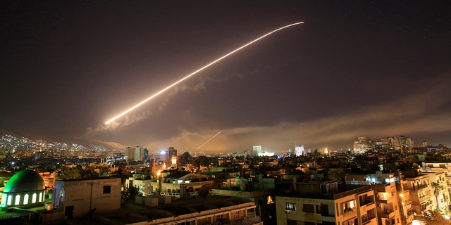 The Damascus sky lights up missile fire as the U.S. launches an attack on Syria targeting different parts of the capital early Saturday, April 14, 2018.  (AP Photo/Hassan Ammar)