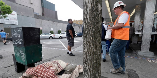 In this May 24, 2018, file photo, a man sleeps on the sidewalk as people behind line-up to buy lunch at a Dick's Drive-In restaurant in Seattle.