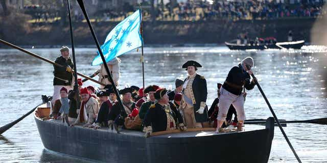 In this Dec. 25, 2016 file photo, John Godzieba, as Gen. George Washington, second right, stands in a boat during a re-enactment of Washington's daring Christmas 1776 crossing of the Delaware River in Washington Crossing, Pa.