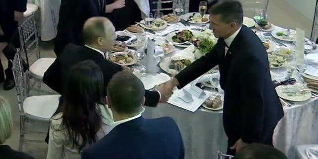 In this image made from a video taken on Dec. 10, 2015 and made available on Tuesday, Feb. 14, 2017, US President Donald Trump's former National Security Advisor Michael Flynn, right, shakes hands with Russian President Vladimir Putin, in Moscow.