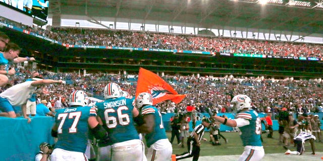 The Miami Dolphins celebrate with running back Kenyan Drake after he scored the winning touchdown during fourth quarter of an NFL football game against the New England Patriots Sunday.