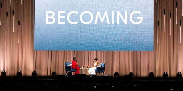 """Former first lady Michelle Obama, left, is interviewed by Phoebe Robinson during the """"Becoming: An Intimate Conversation with Michelle Obama"""" event at the Wells Fargo Center on Thursday, Nov. 29, 2018, in Philadelphia. (Photo by Owen Sweeney/Invision/AP)"""