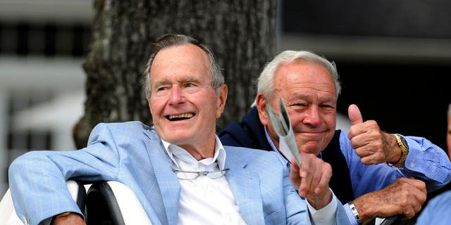 In this Oct. 22, 2010 photo, Former President George H. W. Bush, left, and golfing great Arnold Palmer acknowledge the gallery at the Champions Tour golf tournament in The Woodlands, Texas.