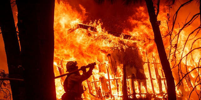 Firefighter Jose Corona spraying water as flames from the Camp Fire consumed a home in Magalia, California, on Nov. 9.