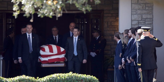 Members of the U.S. Secret Service carry the casket with former President George H. W. Bush to a hearse Monday at George H. Lewis Funeral Home after a family service in Houston. (AP Photo/Kiichiro Sato)