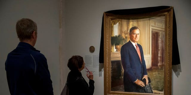 From left, Steve Duensing of Salt Lake City, and Jan Fitzpatrick of Kennebunkport, Maine, look at the official portrait of former President George H.W. Bush as it is draped in black cloth at the National Portrait Gallery in Washington on Monday to mark his passing.