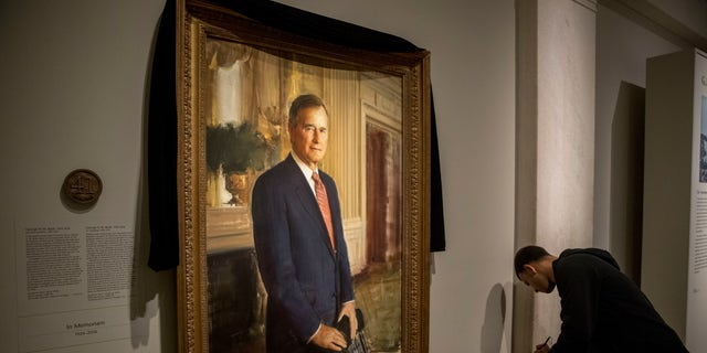 The official portrait of former President George H.W. Bush is draped in black cloth at the National Portrait Gallery before he will lie in state at the Capitol building this week.