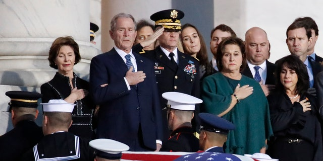Former President George W. Bush and other family members watch as the flag-draped casket of former President George H.W. Bush is carried by a joint services military honor guard to lie in state in the Rotunda of the U.S. Capitol.