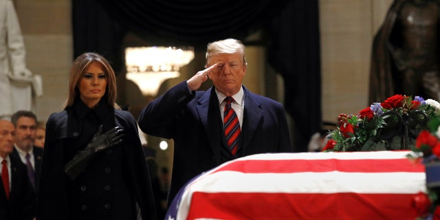 President Donald Trump salutes alongside first lady Melania Trump in front of the flag-draped casket of former President George H.W. Bush in the Capitol Rotunda.