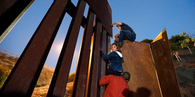 Central American migrants planning to surrender to U.S. border guards climb over the U.S. border wall from Playas de Tijuana, Mexico, late Monday, Dec. 3.