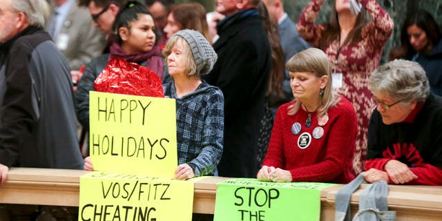 Protesters Peppi Elder, left, and Christine Taylor holds up signs during the state Christmas Tree lighting ceremony in state Capitol Rotunda Tuesday Dec. 4, 2018, in Madison, Wis. The Senate and Assembly are set to send dozens of changes in state law to Gov. Scott Walker's desk. (Steve Apps/Wisconsin State Journal via AP)