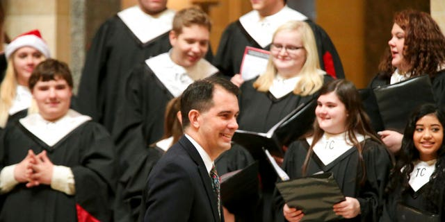 Wisconsin Gov. Scott Walker arrives for the lighting of the state Christmas Tree in the Capitol Rotunda, Tuesday, Dec. 4, 2018 at the Capitol in Madison, Wis. The Senate and Assembly are set to send dozens of changes in state law to Walker's desk Tuesday. (Steve Apps/Wisconsin State Journal via AP)