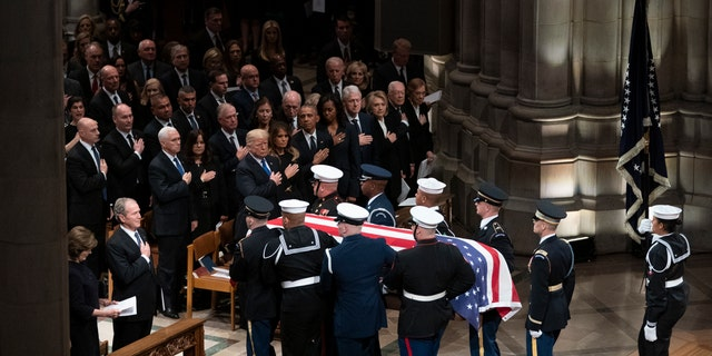 The flag-draped casket of former President George H.W. Bush is carried by a military honor guard past former President George W. Bush and his wife Laura Bush, President Donald Trump, first lady Melania Trump, former President Barack Obama, Michelle Obama, former President Bill Clinton, former Secretary of State Hillary Clinton, former President Jimmy Carter, and Rosalynn Carter at the conclusion of a State Funeral at the National Cathedral.