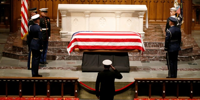 A member of the military pays his respects to the flag-draped casket of former President George H.W. Bush at St. Martin's Episcopal Church.