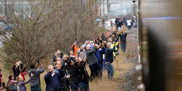 People paying their respects and take photos as the train carrying the casket of former President George H.W. Bush passes on Thursday. The train was making its way from Spring, Texas, to College Station.