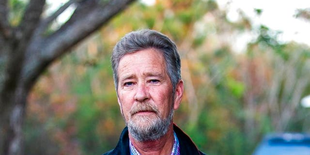 In this Wednesday, Dec. 5, 2018 photo, Leslie McCrae Dowless poses for a portrait outside of his home in Bladenboro, N. C. Focus has centered on Republican operative Dowless, who worked for Harris and returned almost half of absentee ballot requests in a single county last month. Harris had been convicted of insurance fraud in 1992.(Travis Long/The News & Observer via AP)