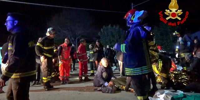 In this frame taken from video rescuers assist injured people outside a nightclub in Corinaldo, central Italy, early Saturday, Dec. 8, 2018.