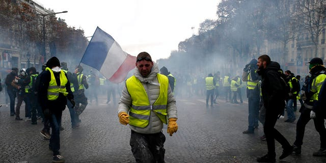 A demonstrator wearing a yellow vest grimaces through tear gas Saturday, Dec. 8, 2018 in Paris. Crowds of yellow-vested protesters angry at President Emmanuel Macron and France's high taxes tried to march Saturday on the presidential palace, surrounded by exceptional numbers of police bracing for outbreaks of violence after the worst rioting in Paris in decades.