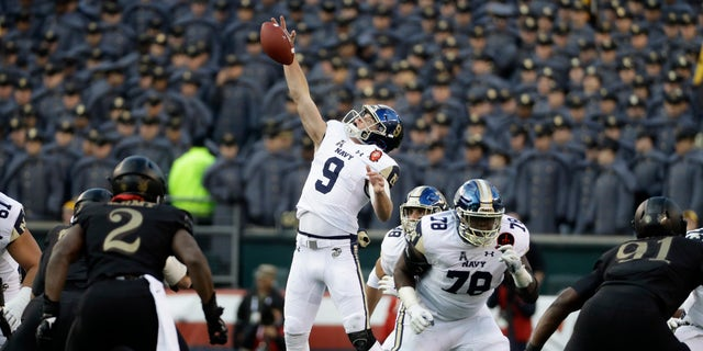 Navy's Zach Abey leaps for a high snap during the first half of an NCAA college football game against Army, Saturday, Dec. 8, 2018, in Philadelphia. (AP Photo/Matt Slocum)