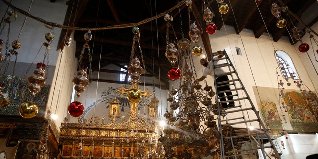 A worker cleans the dust from a chandelier at the Church of the Nativity, built atop the site where Christians believe Jesus Christ was born, in the West Bank City of Bethlehem. (AP Photo/Majdi Mohammed)