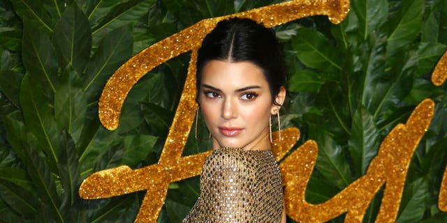 Kendall Jenner poses for photographers upon arrival at The Fashion Awards 2018.