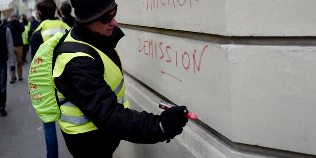 A demonstrator wearing a yellow vest writes a slogan 'Macron resign' on a wall during a protest Saturday, Dec. 15, 2018 in Paris. (AP Photo/Kamil Zihnioglu)