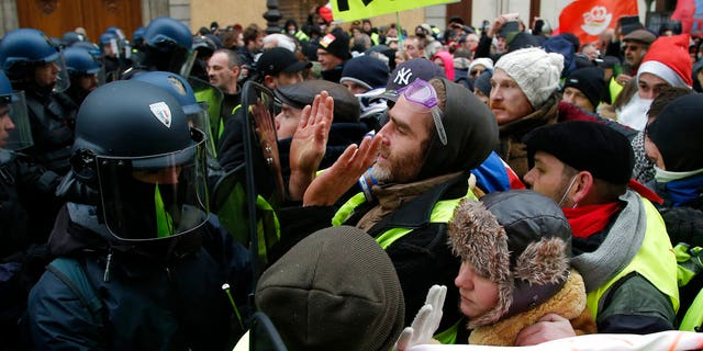 Demonstrators face riot police officers during a protest Saturday, Dec. 15, 2018 in Paris. (AP Photo/Michel Euler)