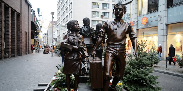 People pass a commemorative memorial statue to perpetuating the memory of the 'Kindertransport' (children transport) near Friedrichstrasse train station in central in Berlin, Germany, Monday, Dec. 17, 2018. Germany has agreed to one-time payments for survivors, primarily Jews, who were evacuated from Nazi Germany as children, many of whom never saw their parents again. (AP Photo/Markus Schreiber)