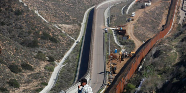A man looks out at the U.S. border where workers are replacing parts of the U.S. border wall for a higher one, in Tijuana, Mexico, Wednesday, Dec. 19, 2018. Workers are reinforcing and changing pieces of the wall where migrants seeking to reach the U.S. have been crossing. (AP Photo/Moises Castillo)