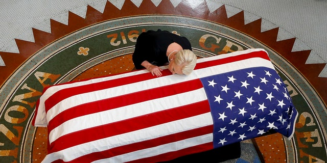 Cindy McCain, wife of the late Sen. John McCain, R-Ariz., rested her head on his casket during a memorial service at the Arizona Capitol.