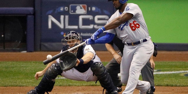 Los Angeles Dodgers batter Yasiel Puig (66) hits a three-run home run during the sixth inning of Game 7 of the National League Championship Series against the Milwaukee Brewers in Milwaukee, in October 2018. Puig, a native of Cuba, has since been traded to the Cincinnati Reds. (Associated Press)