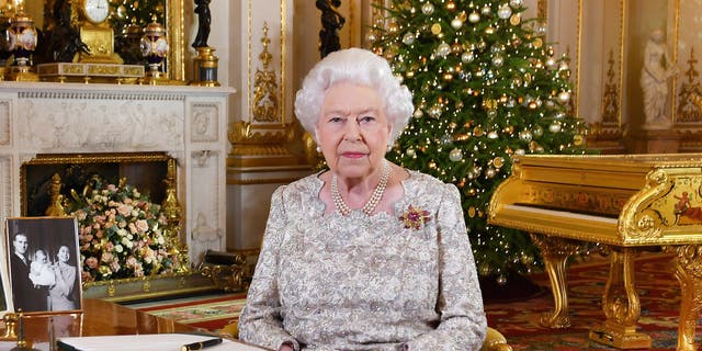 In this photo released on Monday, Dec. 24, 2018, Queen Elizabeth II poses after she recorded her annual Christmas Day message, in the White Drawing Room of Buckingham Palace in central London.