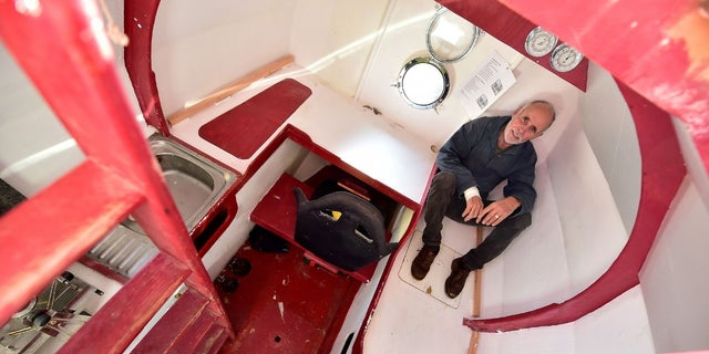 Jean-Jacques Savin shows the inside of the barrel that includes a bunk, kitchen and storage.
