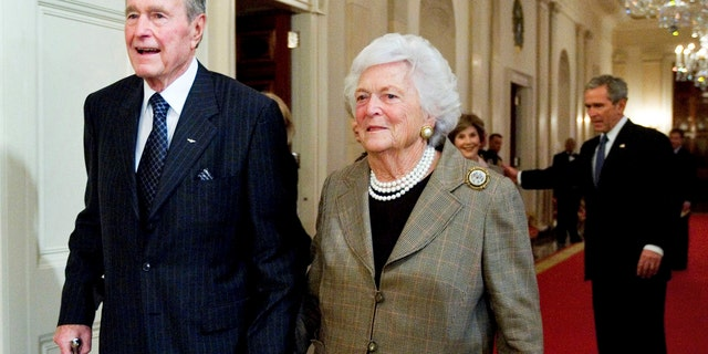 President George H. W. Bush and his wife Barbara Bush, followed by their son, President George W. Bush and his wife first lady Laura Bush, walking to a reception in the White House on Jan. 7, 2009.
