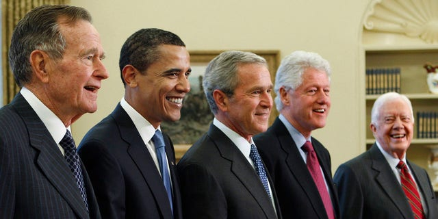 Former president George W. Bush, center, poses with President-elect Barack Obama, second left, and former presidents, George H.W. Bush, left, Bill Clinton, second right, and Jimmy Carter, right, in the Oval Office of the White House in Washington.