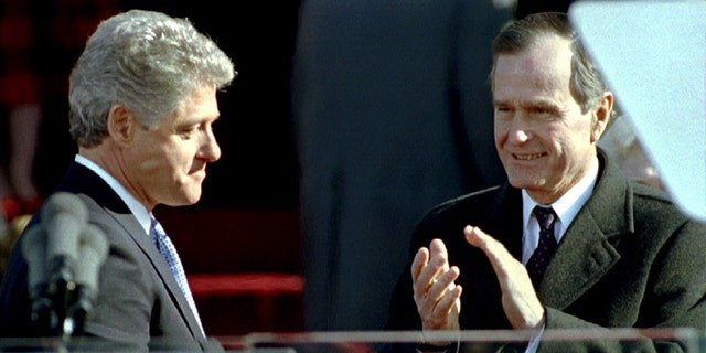 Outgoing President George Bush (R) applauds newly inaugurated President BIll Clinton (L) shortly after his swearing in, January 20