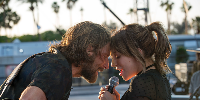 This image released by Warner Bros.  shows Bradley Cooper, left, and Lady Gaga in a scene from the latest reboot of the film, 'A Star is Born'.