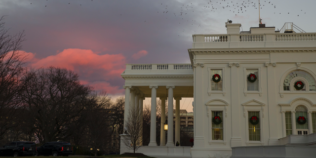 The setting sun illuminates clouds behind the White House during a partial federal shutdown, Dec. 22, 2018, in Washington. (Associated Press)