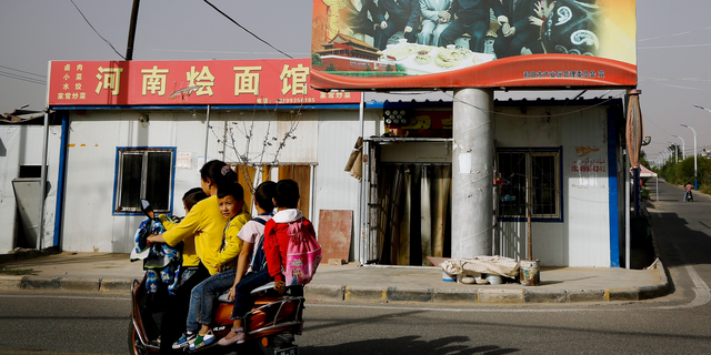 An Uighur woman uses an electric-powered scooter to fetch school children as they ride past a picture showing China's President Xi Jinping joining hands with a group of Uighur elders at the Unity New Village in Hotan, in western China's Xinjiang region. (AP Photo/Andy Wong, File)