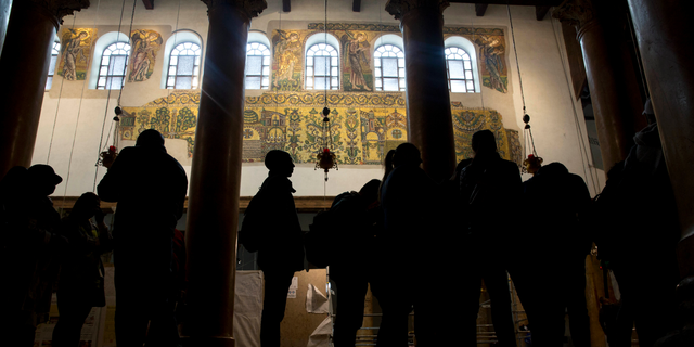 Visitors stand bellow a renovated part of a fresco inside the Church of the Nativity, built atop the site where Christians believe Jesus Christ was born, in the West Bank City of Bethlehem. (AP Photo/Majdi Mohammed)