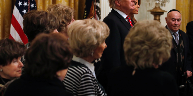 President Donald Trump and first lady Melania Trump are joined by Holocaust survivors, as they attend a Hanukkah reception, Thursday, Dec. 6, 2018, in the East Room of the White House in Washington.