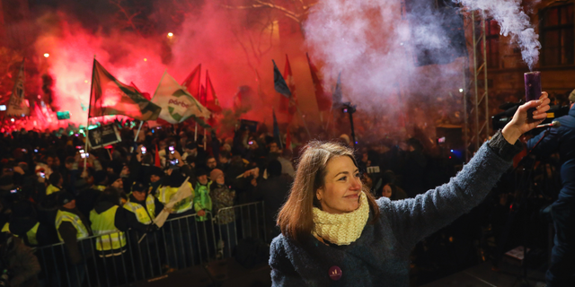 Vice-chairperson of Momentum party Anna Donath holding up a smoke grenade during an anti-government protest in downtown Budapest on Sunday. (Balazs Mohai/MTI via AP)