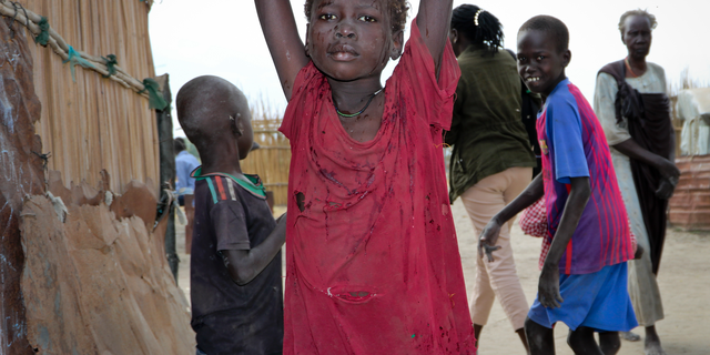 In this photo taken Sunday, Dec. 9, 2018, a young girl carries water on her head in Koythiey displaced person's camp on the outskirts of Bentiu town in South Sudan. Six months ago planning ahead in civil war-torn South Sudan seemed impossible but now, after warring sides signed a new peace deal in September that the government vows will hold, some are starting to rebuild their lives.
