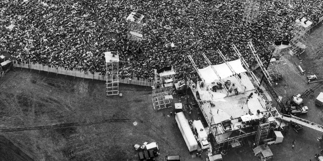 Music fans pack around the stage at the original Woodstock Music and Arts Festival, lower right, in Bethel, N.Y., on August 16, 1969.
