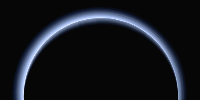 FILE - This image made available by NASA in March 2017 shows Pluto illuminated from behind by the sun as the New Horizons spacecraft travels away from it at a distance of about 120,000 miles (200,000 kilometers). (NASA/Johns Hopkins University Applied Physics Laboratory/Southwest Research Institute via AP)