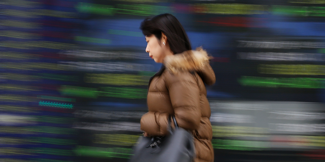 """A woman walks by an electronic stock board of a securities firm in Tokyo, Wednesday, Dec. 26, 2018. Asian markets were mostly lower on Wednesday after President Donald Trump said that there was """"nothing new"""" in efforts to end the partial government shutdown over a U.S.-Mexico border wall. (AP Photo/Koji Sasahara)"""