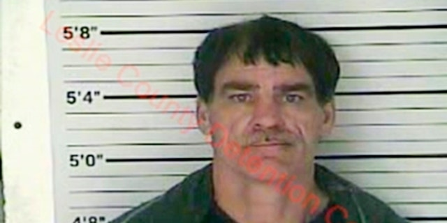 In this Wednesday, Dec. 12, 2018 photo released by the Leslie County (Ky.) Detention Center, Paul Douglas Sizemore is seen in a booking photo. Sizemore, accused of shooting at a state police trooper rushing to the scene of a triple slaying has been charged in the murders of an eastern Kentucky couple and their adult son, police said Thursday. (Leslie County Detention Center via AP)