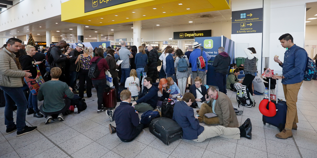 People wait outside the departures gate at Gatwick airport, near London, as the airport remains closed with incoming flights delayed or diverted to other airports, after drones were spotted over the airfield last night and this morning, Thursday, Dec. 20, 2018. London's Gatwick Airport remained shut during the busy holiday period Thursday while police and airport officials investigate reports that drones were flying in the area of the airfield.