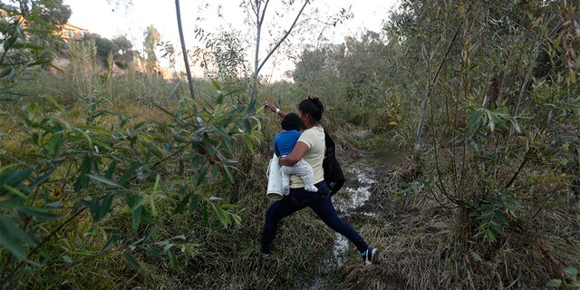 Yesenia Martinez, 24, carrying her eight-month-old son Daniel as she looked for a place to cross the U.S. border wall. (AP Photo/Rebecca Blackwell)