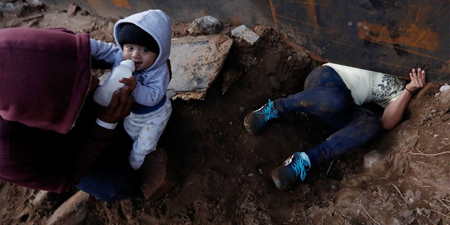 Honduran migrant Joel Mendez, 22, feeding his eight-month-old son Daniel as his partner Yesenia Martinez, 24, crawled through the hole under the U.S. border wall. (AP Photo/Rebecca Blackwell)